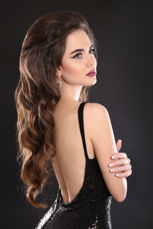 Beautiful brunette portrait. Elegant sexy woman in black dress with open back. Back view of Attractive girl model with makeup, long wavy hair style isolated on dark background. Stock Photo