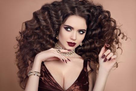 Maquillage de beauté. Cheveux bouclés. Portrait à la mode glamour du modèle de belle femme brune avec des lèvres marsala mat et bijoux fantaisie doré isolé sur fond beige.