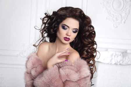 Woman in fur coat. Curly hair. Beautiful Brunette Girl portrait. Manicured nails. Beauty glitter eyeshadows makeup. Long healthy Hairstyle. Fashion brunette posing in white interior.