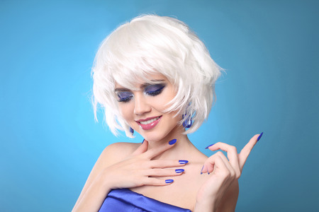 Short Hairstyle. Fun smiling blond. Makeup. Closeup of beauty fashion girl with bob short hair style and glitter eyeshadow, manicured nails over blue studio background.