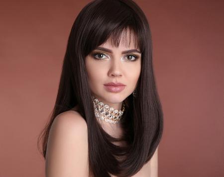 化粧。髪型。美人美少女ブルネット肖像画.ファッションゴールデンジュエリー。スタジオの背景に分離された健康な茶色のヘアスタイルを持つセク 写真素材