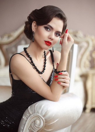 Elegant lady. Beauty fashion glamour girl portrait. Sexy brunette with red lips makeup, retro wave hairstyle, manicured nails, expensive black gems jewelry set posing in luxury interior.