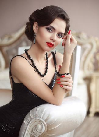 Femme élégante. Portrait de jeune fille glamour fashion beauté. Brunette sexy avec le maquillage des lèvres rouges, coiffure rétro vague, ongles manucurés, ensemble de bijoux coûteux de pierres précieuses noires posant dans un habitacle