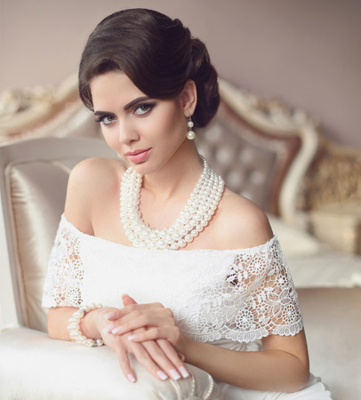 Beautiful brunette, elegant woman portrait. Fashion pearl jewelry set. Retro lady with makeup, wavy hairstyle in white sexy dress posing on modern bed in luxurious interior.  Stock Photo