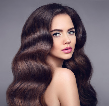 Beauty long wavy hair. Elegant Brunette girl portrait with healthy shiny hairstyle. Beautiful model with makeup isolated on studio dark background. Shampoo care product. Stock Photo