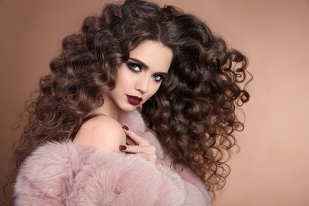 Hairstyle. Beauty hair. Fashion brunette girl with long curly hair, beauty makeup. Glamour portrait of beautiful woman with marsala matte lips in pink fur coat isolated on beige background.