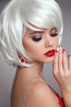 Christmas makeup. Red lips Makeup. Beautiful blond closeup portrait. Manicured nails. Jewelry. White Short bob hairstyle. Sensual blonde woman with xmas eye shadow. Vogue style.
