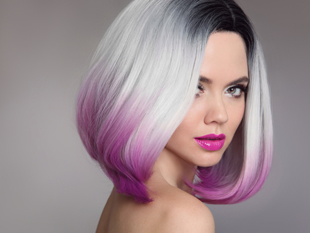 Colored Ombre hair extensions. Beauty Model Girl blonde with short bob purple hairstyle isolated on gray background. Closeup woman portrait.