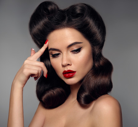 Nostalgia. Pin up girl with red lips makeup and retro curls hair style. Retro woman looking to the side holds a finger near the head. Expressive facial expressions. High fashion photo.