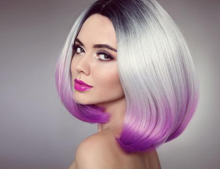 Bob peinado. Extensiones de cabello color Ombre. Rubia de belleza modelo chica con estilo de pelo púrpura corto aislado sobre fondo gris. Closeup retrato de mujer.