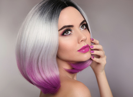 Ombre hairstyle. Beauty makeup and manicure nails. Colored blonde bob short hair style. Portrait of glamour woman with purple lipstick and polish nail. Фото со стока