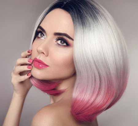 Colored Ombre bob hair extensions. Manicure nails. Beauty makeup. Attractive Model Girl blonde with short pink hairstyle isolated on gray background. Closeup woman portrait. Stock Photo