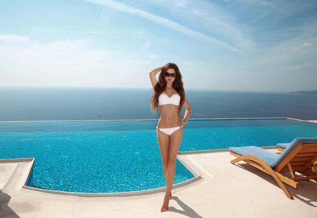 Beautiful sexy woman bikini model with long healthy hair, brunette posing and tanned by the blue swimming pool, summer vacation. Fit body. Healthy body care. Luxury life resort.