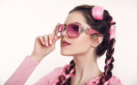 Brunette teen girl with two french braids from pink kanekalon, fashionable hairdo for youth, creative hairdresser beauty salon. Attractive female with fashion sunglasses isolated on white background.