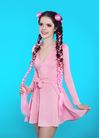 Pretty teen girl with two french braids from pink kanekalon, fashionable hairdo for youth, creative hairdresser beauty salon. Positive brunette posing in cute dress isolated on blue studio background. Stock Photo