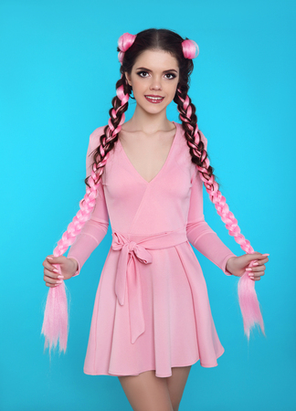 Pretty teen girl with two french braids from pink kanekalon, fashionable hairdo for youth, creative hairdresser beauty salon. Positive brunette posing in cute dress isolated on blue studio background. Stok Fotoğraf