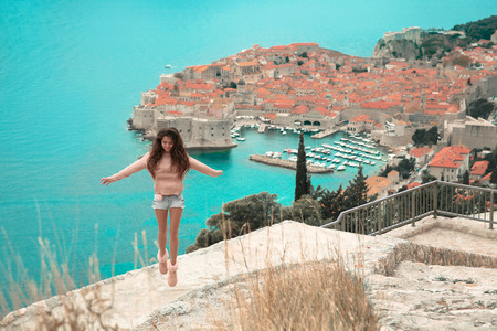 Brunette Girl tourist visiting mountain viewpoint  sightseeing in Dubrovnik, Croatia. Woman traveller in front on famous travel destination. Free brunette  enjoying vacation.  Europe Lifestyle.