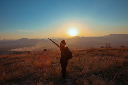 Sunset mountain. Tourist Free happy  woman outstretched arms with backpack enjoying life in wheat field. Hiker cheering elated and blissful with arms raised at sunrise.