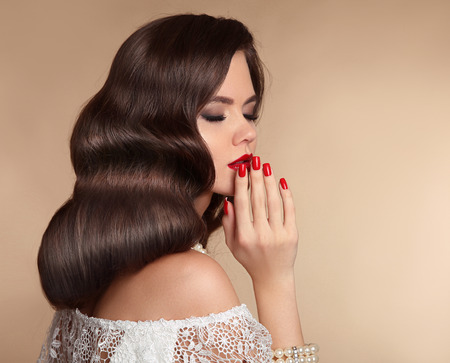 Elegant woman with red lips makeup, manicured nails and retro wavy hair style. Sensual alluring brunette present your ring jewelry product isolated over beige background.