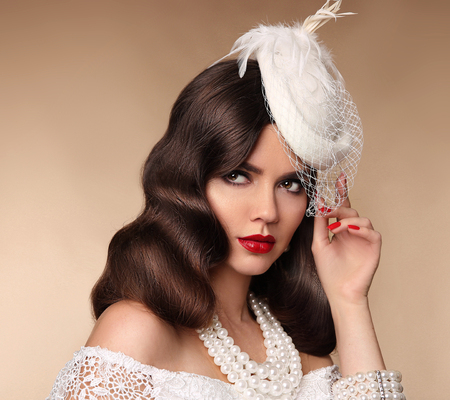 Elegant woman portrait in retro hat. Pin up girl wears in pearls jewelry, wavy hairstyle and red lips makeup. Brunette lady isolated beige background.