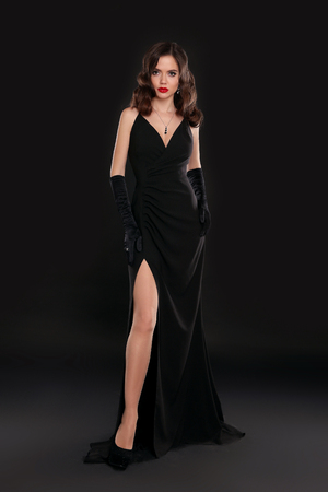 Elegant lady in long sexy dress with retro wavy hairstyle posing isolated on studio black background. Beautiful brunette woman in glamour gloves. Fashion style full length photo.