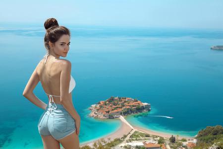Beautiful destination. Tourist girl sightseeing Sveti Stefan island in Budva, Montenegro. Sexy brunette traveller visiting Adriatic Sea,  Balkans. Summer travel vacation background. 스톡 콘텐츠