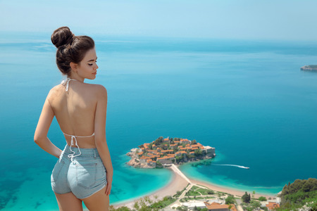 Beautiful tourist girl sightseeing Sveti Stefan island in Budva, Montenegro. Sexy brunette traveller visiting Adriatic Sea,  Balkans. Summer travel vacation background.