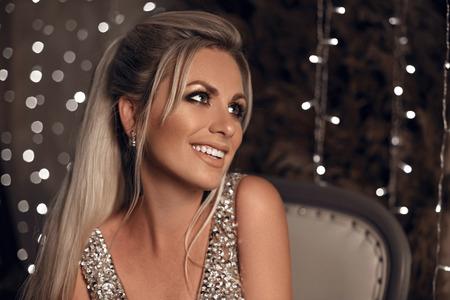 Retrato de hermosa mujer rubia feliz riéndose de la cámara sobre fondo de Navidad de luces bokeh. Modelo de joyería.