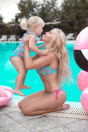 Beauty fashion mother with daughter family look. Beautiful blond woman with having fun with little pretty gil wears in swim wear posing by swimming pool on chill beach. Summer time vacations.