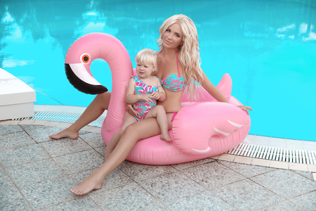 Beauty fashion mother with daughter family look. Beautiful blond woman with having fun with little pretty gil wears in swim wear posing on Inflatable Flamingo Pool Float by swimming pool.
