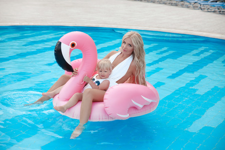 Beauty fashion mother with daughter family look. Beautiful blond woman with having fun with little pretty gil wears in swim wear posing on Inflatable Flamingo Pool Float in swimming pool.