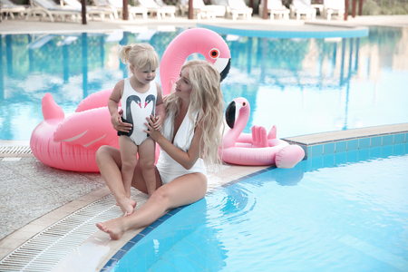 Beauty fashion mother with daughter family look. Beautiful blonde pretty woman having fun with adorable little girl  wears in white swimwear having fun by swimming pool on luxury resort. Standard-Bild