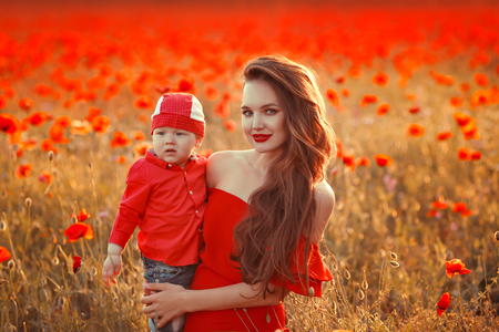 Mother with son in poppies enjoying life at sunset. Happy family summer vacation. Pretty brunette with long healthy hair holding little boy. Carefree young mom over red field. Countryside landscape.