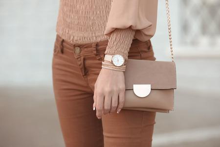 Look alla moda vestito da donna autunnale. Elegante borsa da donna beige. Primo piano di orologi di lusso e accessori femminili in color pastello. Simpatica borsa da donna beige.