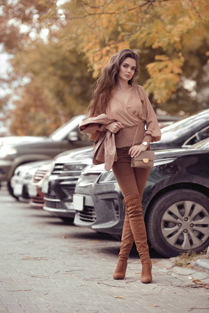 Beautiful stylish woman. Fashion outfit, autumn trend. Young casual brunette walking by cars in street. Fashion girl holding purse, wearing brown trousers, pastel blouse and luxurious accessories.