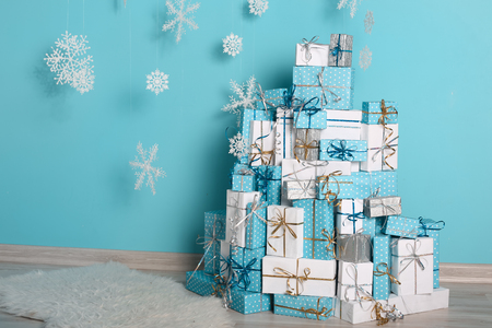 Christmas copyspace interior and decorations. Snowflakes and gift boxes with bow in front of by wall turquoise wall in holiday winter modern room. Postcard Xmas background.