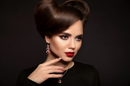 Elegant lady with jewelry set. Beautiful woman with makeup and retro hairstyle, presenting precious earrings and necklace isolated on studio dark background. Beauty and accessories.