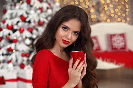 Christmas portrait. Beautiful happy girl with cup. Smiling pretty woman with long hair and red lips makeup drink warm coffee in home by xmas snow over boke lights background. Happy New Year!