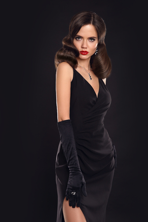 Elegant lady in long dress with retro wavy hairstyle posing isolated on studio black background. Fashionable glamour model. Beautiful brunette woman in glamour gloves. Fashion style photo.