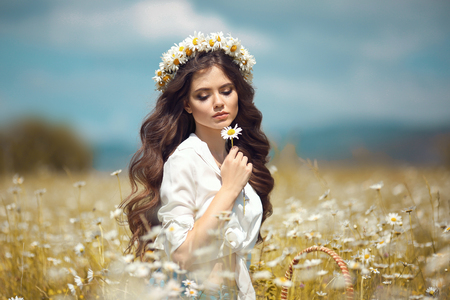 Beautiful young girl with flower enjoying in chamomile field. Carefree happy brunette woman with chaplet on healthy wavy hair having fun outdoor in nature. People freedom style.