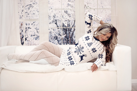 Winter woman indoor portrait. Young beautiful blond girl in warm knitted clothes by snow window at home. Fashion style cloth.