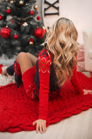 Healthy hair. Curly long hairstyle. Back view Christmas portrait of attractive woman with curly hairstyle. Beutiful blond girl  wears in warm red knit woolen sweater.