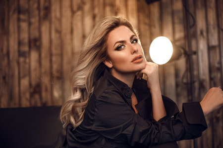 Gorgeous model. Blond woman portrait in black shirt. Fashionable girl with beauty makeup and curly hair style posing in wooden dark interior.