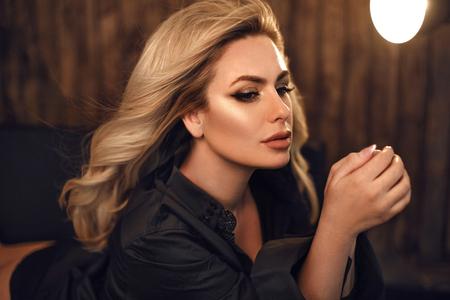 Preciosa modelo. Retrato de mujer rubia en camisa negra. Chica de moda con maquillaje de belleza y peinado rizado posando en interior oscuro de madera.
