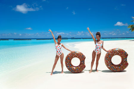 Summer Vacation. Happy free two women with donut float mattress enjoying exotic beach by turquoise water seaside. Maldives island paradise background. Beautiful destinations.