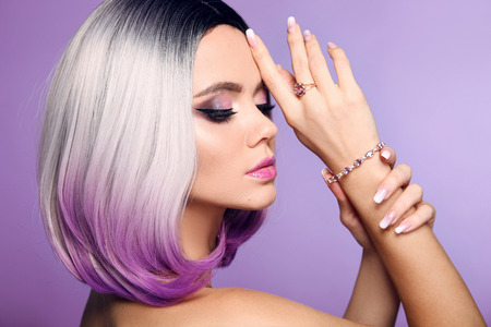 Beautiful lady presents amethyst ring and bracelet jewelry set. Woman portrait with ombre bob short hairstyle and manicured nails. Beauty makeup. Gorgeous model isolated on purple background. Foto de archivo