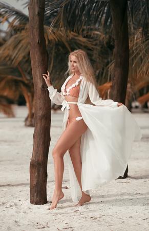 Attractive blond woman with long legs. Slim girl wears white swimwear posing on tropical Maldives beach. Stock Photo