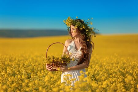 Beautiful young woman with wreath on long healthy hair over Yellow rape field landscape background. Attracive brunette girl with curly hairstyle holding basket with flowers, outdoor portrait. Zdjęcie Seryjne