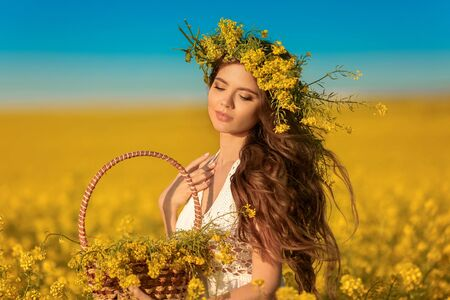 Beautiful young woman with wreath on long healthy hair over Yellow rape field landscape background. Attracive brunette girl with blowing hairstyle holding basket with flowers, outdoor portrait.