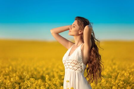 Beautiful carefree girl with long curly healthy hair over Yellow rape field landscape background. Attracive brunette with blowing hairstyle enjoying and breathing sunset, outdoor beauty portrait. Stock fotó